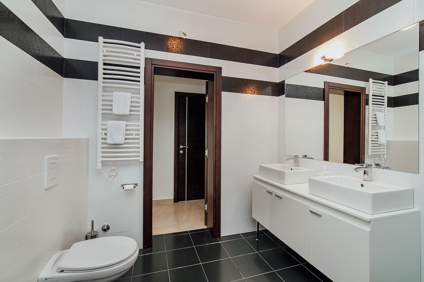 badkamer met bad, inloopdouche, toilet en dubbele wastafel